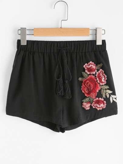 Shorts avec des franges et un lacet et des appliques des roses