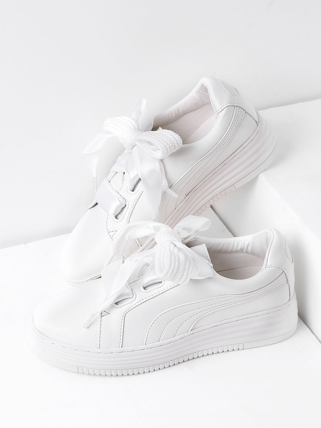 white trainers with a bow lace